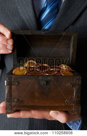 Businessman Holding Wooden Chest With Gold Coins Inside