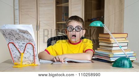 Confused schoolboy in funny glasses screaming near the huge stack of books. Education. Boy Having Pr