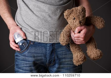 Father Holding Feeding Bottle And Teddy Bear