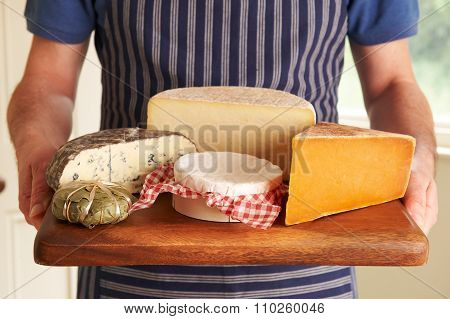 Grocer Holding Board With Selection Of Luxury Cheeses