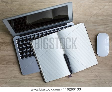 Laptop and Notepad with pen are on the table. Space for your text on the Notepad.