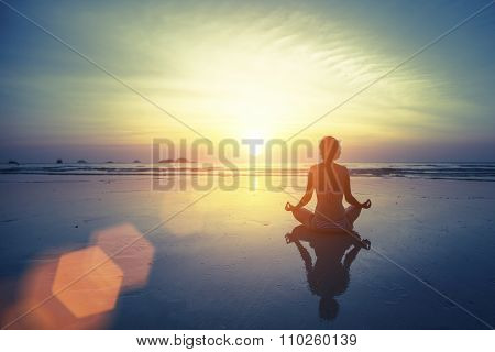 Silhouette meditation yoga woman on the background of the sea and amazing sunset. Healthy lifestyle.