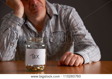 Depressed Man Looking At Empty Jar Labelled Tax