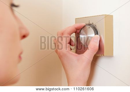 Woman Adjusting Central Heating Thermostat Control