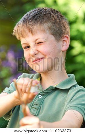 Boy Aiming Slingshot In Garden