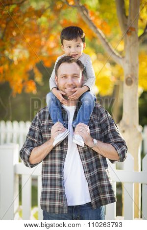 Happy Mixed Race Boy Riding Piggyback on Shoulders of Caucasian Father.