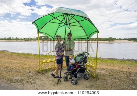 Young Father , Mother And Son 1.3 Years By The River Under A Big Umbrella In  Gazebo.