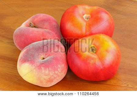 Saturn Peaches, known as flat Donut peach and Flat Nectarines on a wooden background