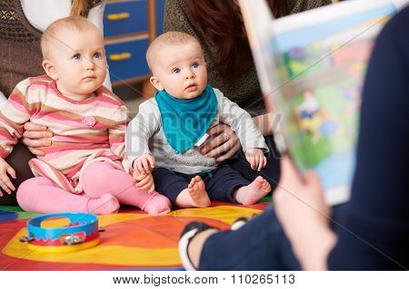 Mothers With Children At Baby Group Listening To Story