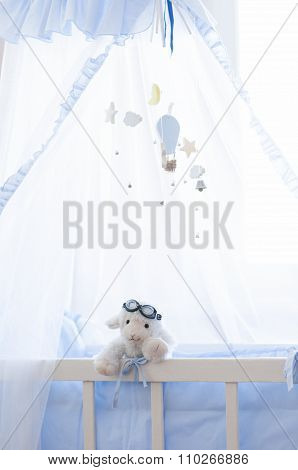 Baby wooden cot with hanging wooden toys.