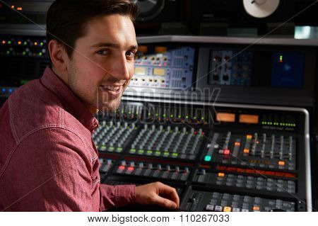 Engineer Sitting At Mixing Desk In Recording Studio