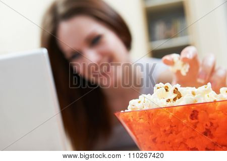 Woman Eating Popcorn Whilst Watching Movie On Laptop
