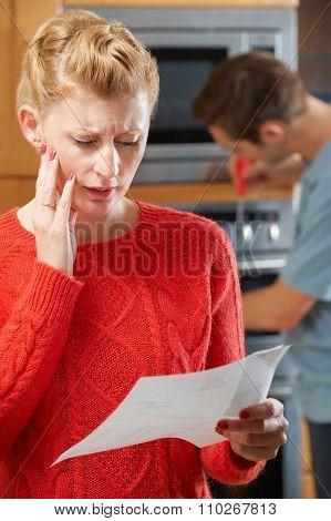 Worried Woman Looking At Repair Bill