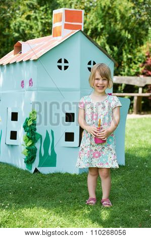 Young Girl Painting Cardboard Playhouse In Garden