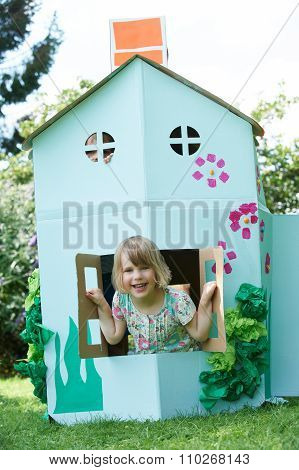Two Children Playing In Home Made Cardboard House
