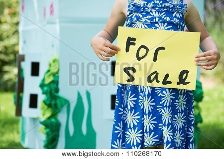 Little Girl Holding For Sale Sign Outside Cardboard Playhouse