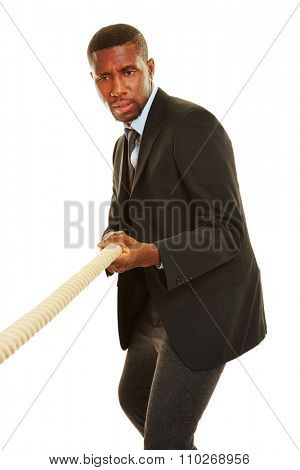 African business man playing tug of war and pulling on a rope