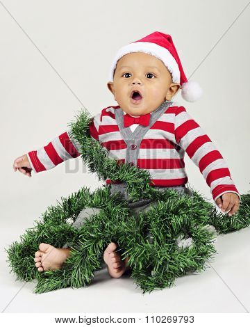 An adorable baby wearing a Santa hat and wrapped in Christmas garland.  On a gray background.