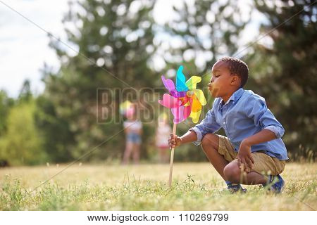 African boy blows at his pinwheel and plays