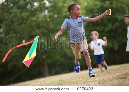 African kid having fun flying a kite in the nature