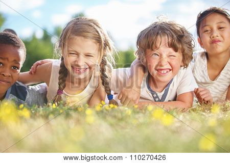 Interracial group of children in summer on the grass