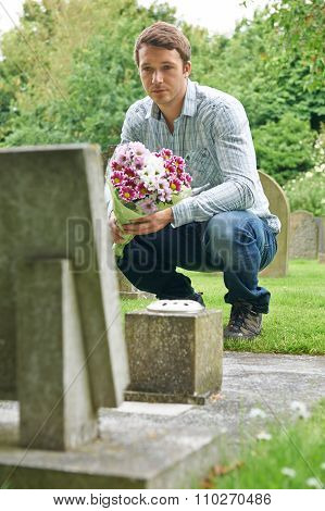 Man Laying Flowers At Grave