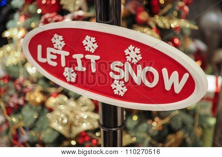 Close Up Of Christmas Decorations. Sign Let It Snow