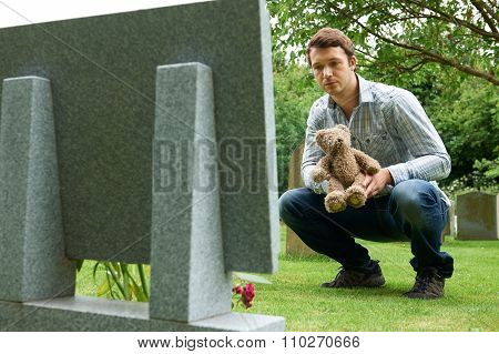 Father Placing Teddy Bear On Child's Grave In Cemetery