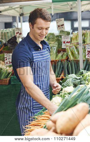 Stall Holder Arranging Display At Vegetable Market