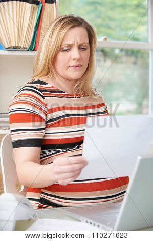 Concerned Pregnant Woman Working In Home Office