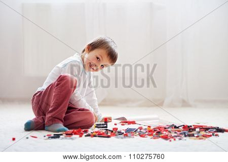 Little Child Playing With Lots Of Colorful Plastic Blocks Indoor, Building A Fire Truck And A Fire H