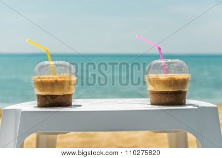 Two Ice Frappe Coffee Cups On Beach