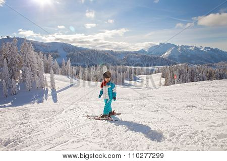 Adorable Little Boy With Blue Jacket And A Helmet, Skiing
