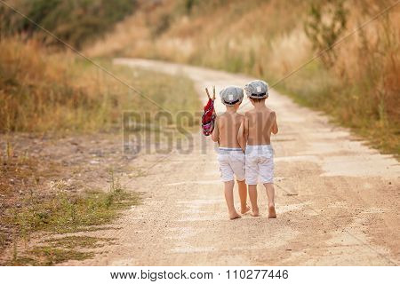 Two Cute Little Boys,brothers, Holding A Bundle, Eating Bread And Smiling, Walking Bare Feet On A Du