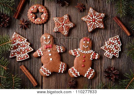 Gingerbread man and woman couple, fur trees, star, christmas cookies composition with xmas tree deco