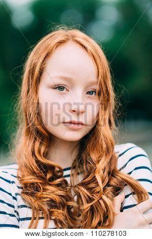 An Adorable Smiling Young Woman With Green Eyes And Long Curly Red Hair In Summer Park