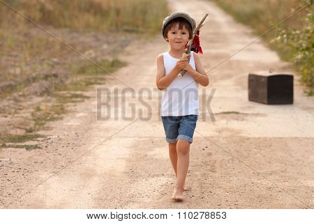 Cute Little Boy, Holding A Bundle, Eating Bread And Smiling, Walking Bare Feet On A Dusty Road