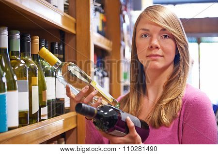 Woman Choosing Between Red And White Wine In Supermarket