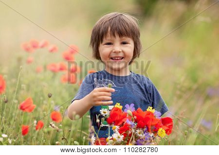 Cute Kid Boy With Poppy Flowers And Other Wild Flowers In Poppy Field On Warm Summer Day
