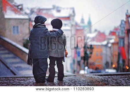 Two Kids, Standing On A Stairs, View Of Prague Behind Them, Snowy Evening