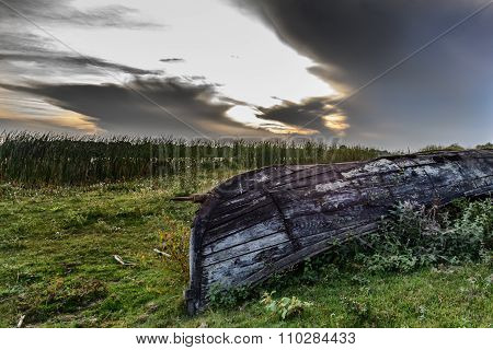 One Cracked, Old Boat, Turned Upside Down On The Shore. Vertical View Of An Old And Cracked Shell Of