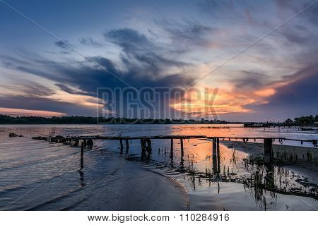 Wooden Pier At Sunset In The Summer. Horizontal View Of A Wooden Pier Near A Muddy Shoreline Over Su