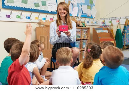 Teacher Showing Flashcard To Elementary School Class