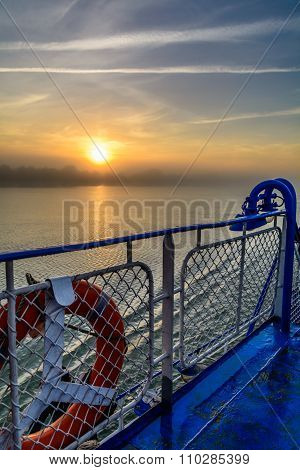Sunset View From The Edge Of A Boat's Deck. Vertical View Of A Foggy Sun-setting Background In A Sum