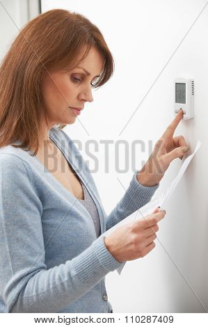 Worried Woman With Heating Bill Turning Down Thermostat