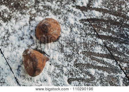 Two Chocolate Truffles On The Wooden Background