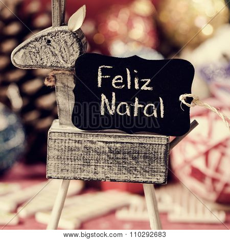 a black label with the text feliz natal, merry christmas in portuguese, on a rustic wooden reindeer, with some different christmas ornaments in the background