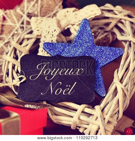 a black label with the text joyeux noel, merry christmas in french, on a pile of gifts and different bonnie christmas ornaments