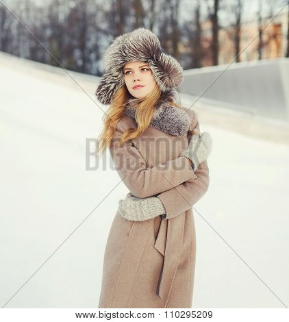Beautiful Woman Wearing A Hat And Coat Jacket Over Snow In Winter City