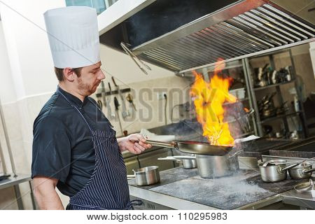 Food preparation. Chef cook in restaurant kitchen with pan over stove doing flambe